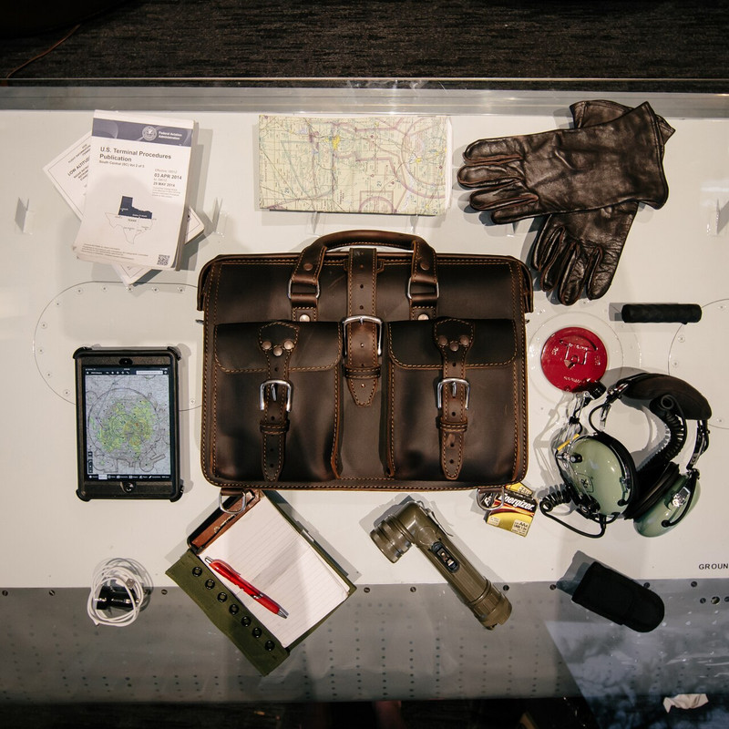 This is a red brown leather briefcase sitting on a table with all of the things it can hold laying all around it.