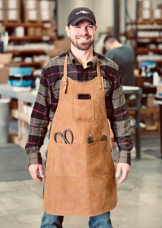 This is the front view of the Simple Leather Apron in brown on someone.