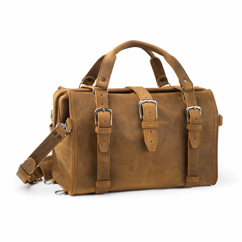 This is a tan brown overnight leather duffle bag with a gladstone closure from the front view.