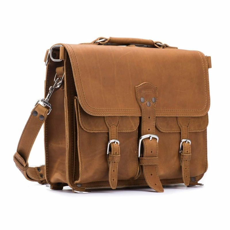 This is the front side of a light tan brown leather briefcase with front pockets and a buckle in the middle.