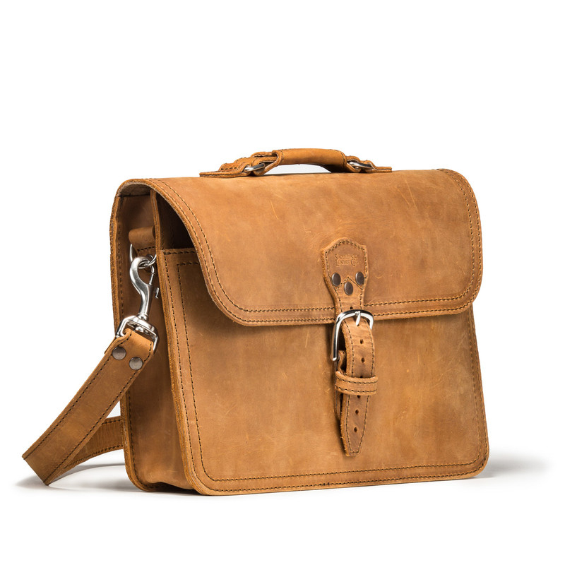 This is the front of a slim tan brown leather briefcase slightly angled.
