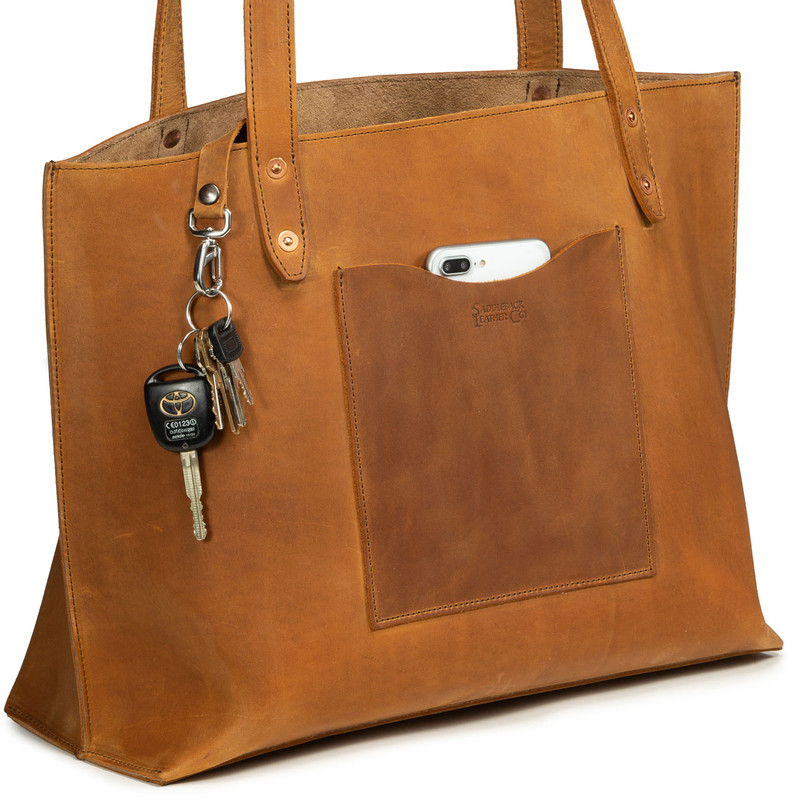 This is a tan brown women's leather tote bag purse with a pocket on the front and showing the side.
