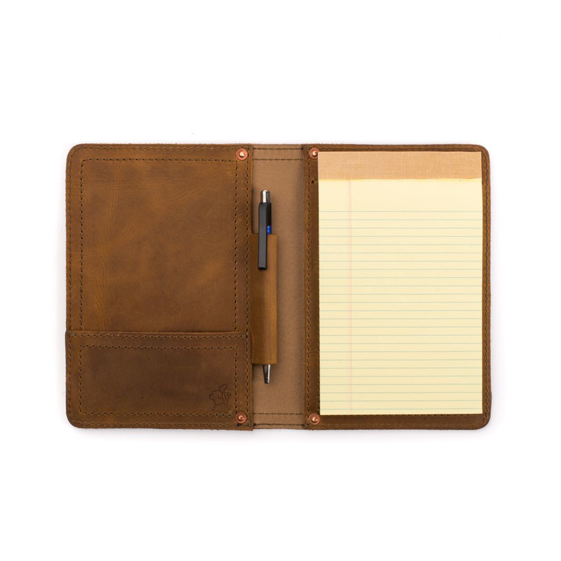 The small tan brown leather portfolio is wide open with a pad of paper in it which is known also as a padfolio.
