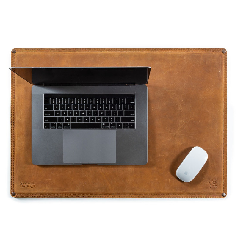 This is a leather desk pad with a laptop and a mouse on it.