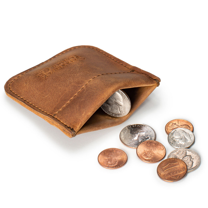 This is a tan brown leather coin purse that has change spilling out in front of the pouch.