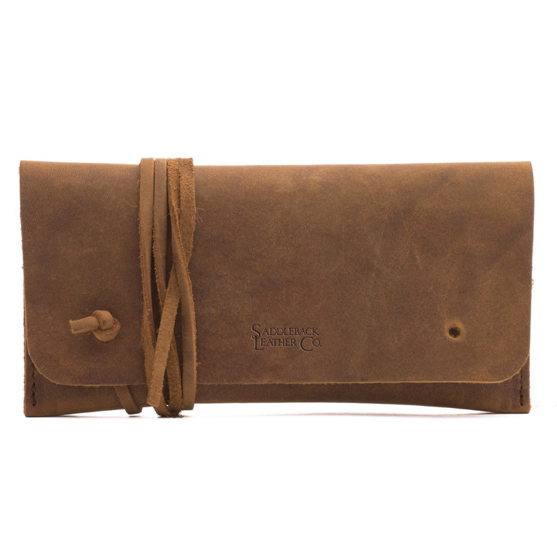 This is a tan brown leather wallet bag with a wrap around it to close it from the front.