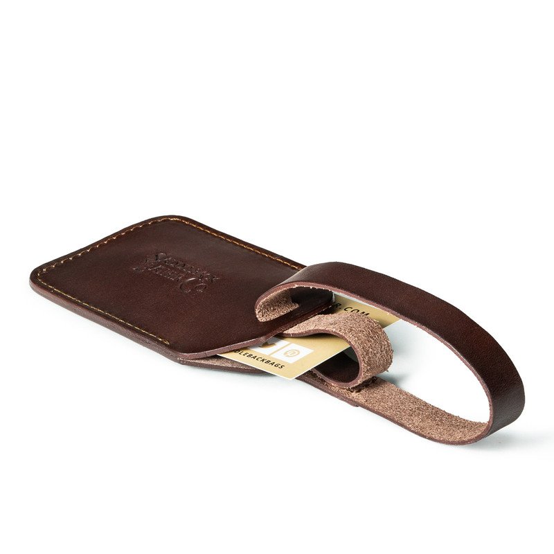 This is a dark brown leather luggage tag made of vegetable tanned leather laying down.
