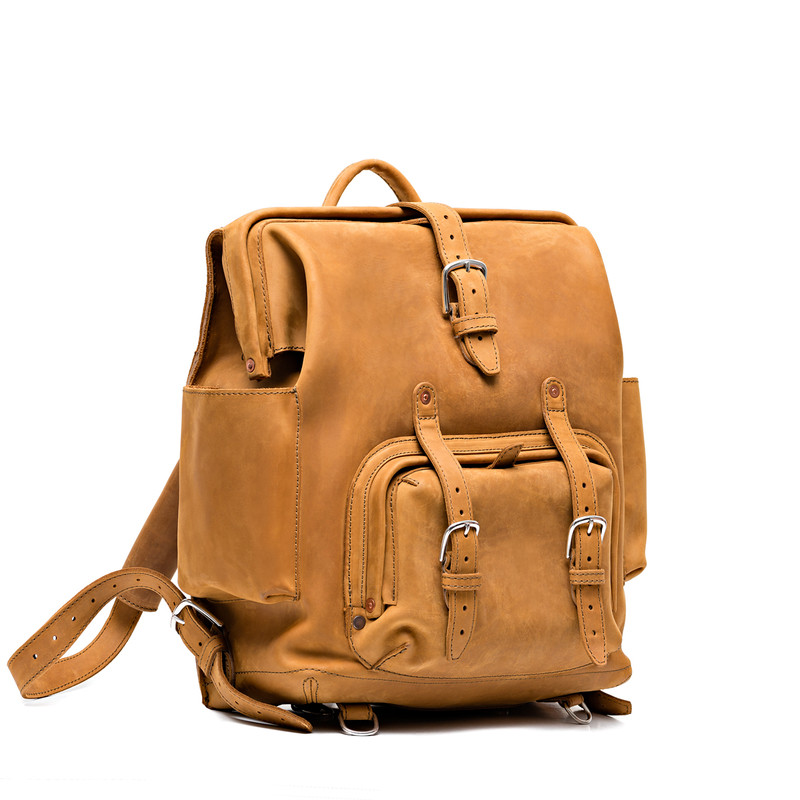 This is a tan brown leather backpack with a pocket on the front side.