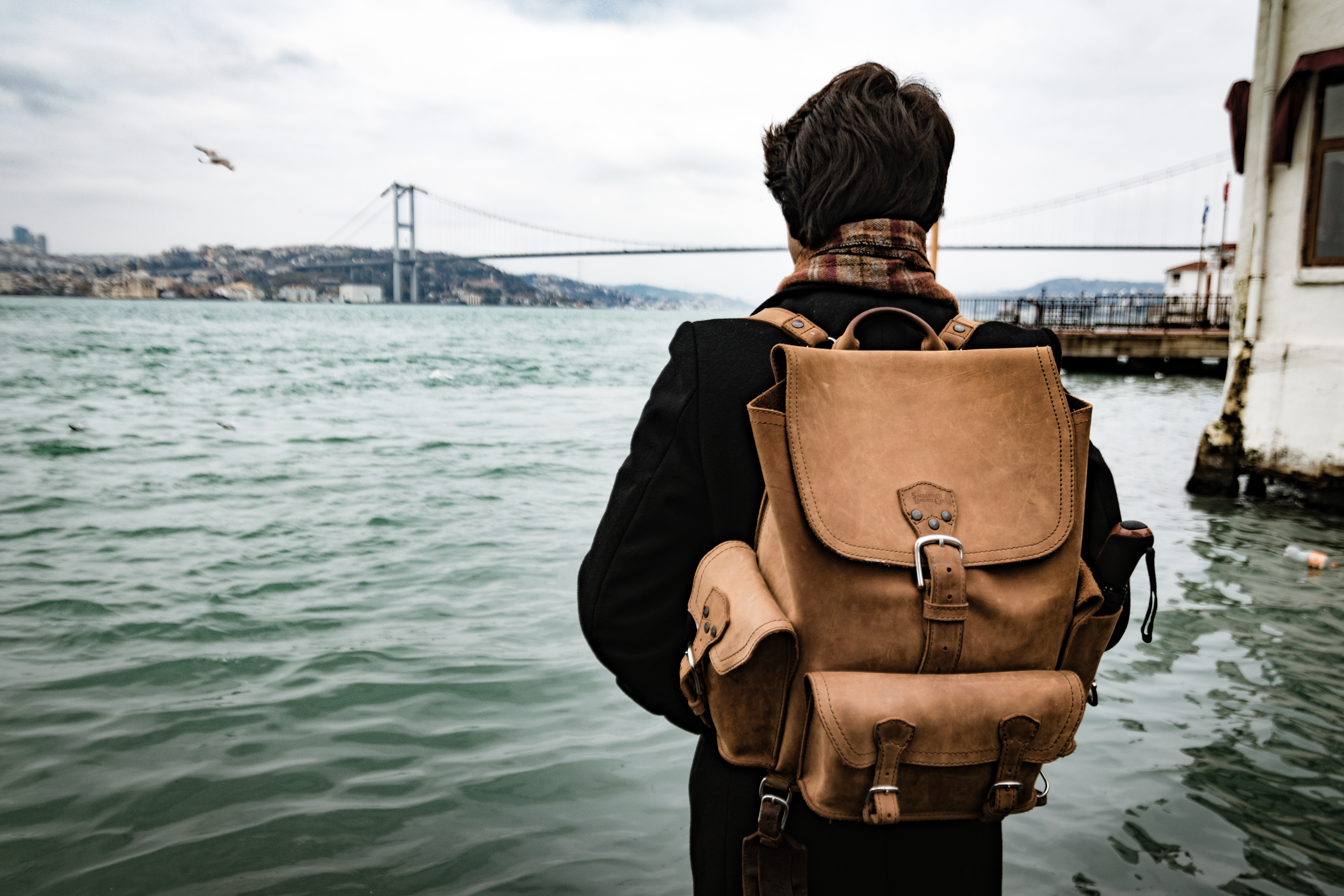 leather rucksack backpack on man by bridge