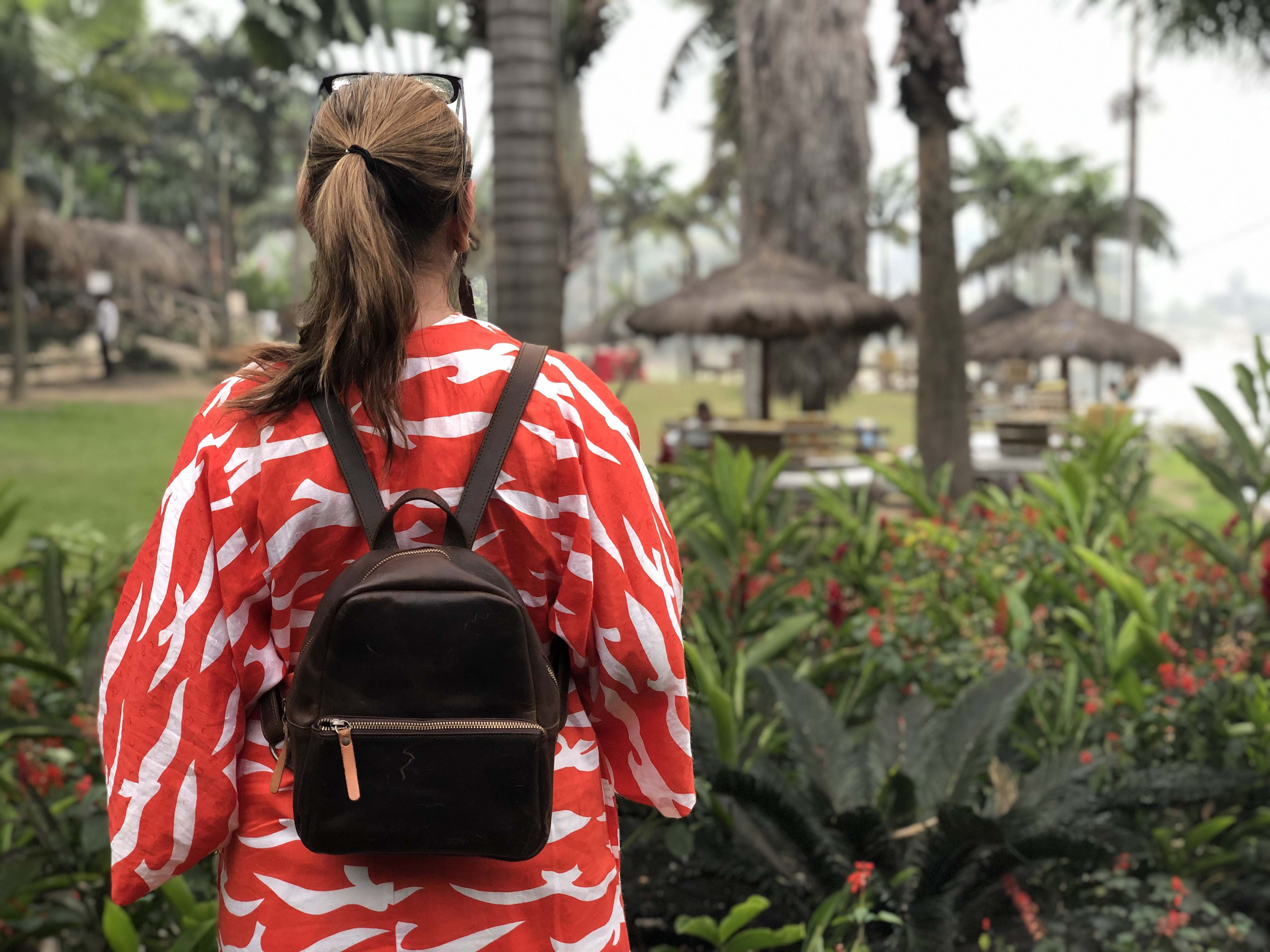 Leather Women's backpack that is on a woman with a red dress in Africa