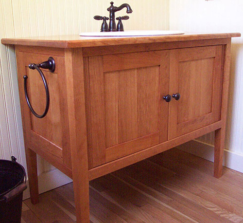 Solid cherry vanity with cherry top, single sink and double doors. Hardware is Oil Rubbed Bronze.