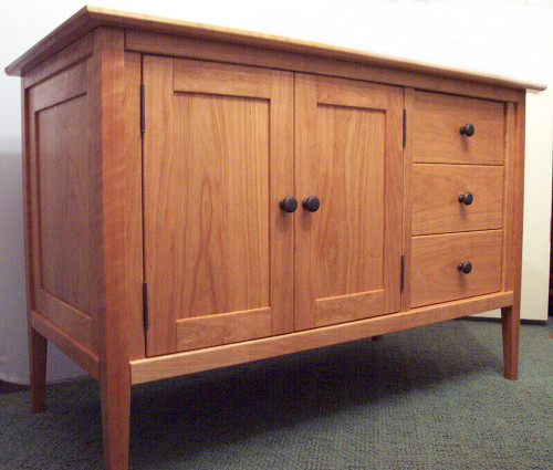"""Solid cherry vanity is 48"""" wide with solid cherry top, single sink and double doors.  There is also a stack of three functional, soft close drawers. Hardware is Oil Rubbed Bronze."""