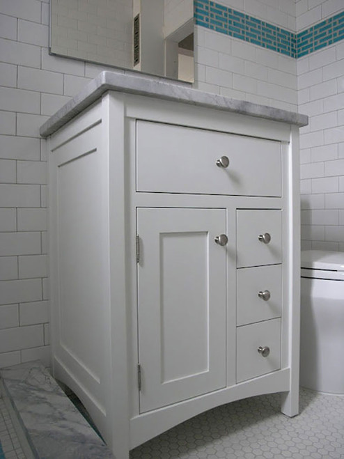 "A 24"" painted poplar, shaker style vanity with one door, 1 false drawer, and 3 functional drawers adding an incredible amount of usable storage to a very small space. Also shown are square legs and optional arched base rails."