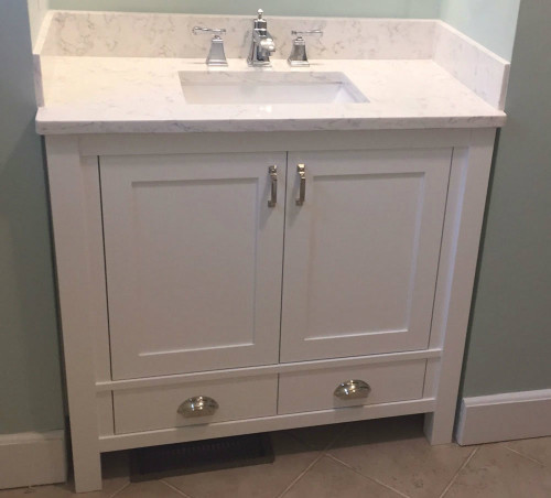 """Only 32"""" wide but takes advantage of every inch of storage space by putting drawers below the doors.   Although available in any wood and finish, this particular vanity is built from solid poplar; and by choosing square legs together with beadboard panel doors and ends, and finishing it all with Snow White Milk Paint, lightly distressed, a traditional shaker style vanity is transformed, giving it a classic cottage style look."""