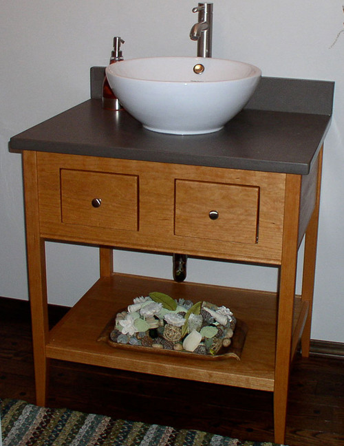 "This 29"" wide, single height apron open style vanity is made from solid cherry, has two functional drawers with satin nickel knobs, and a solid shelf. The top is made from a product called Earthcrete. Even though the vanity is narrow, by having a vessel sink it allows both drawers to be functional."
