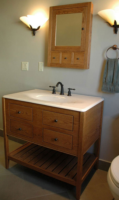 "A 38"" double height apron, open style vanity with a slat shelf. This particular one is made of white oak stained with a Nutmeg finish. The two bottom drawers are functional. The top drawers are false to allow room for the sink basin. The medicine cabinet is our recessed combo 6"" deep cabinet which only needs a 4"" deep wall cavity because the other 2"" remain on the outside of the wall. This one also has the optional apothecary drawers."