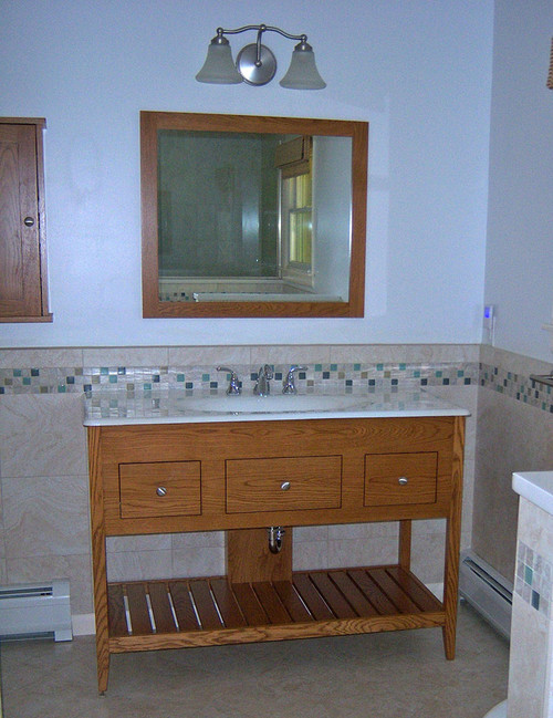 """This open style vanity is made with an extra deep 14"""" apron which allows for two wider than usual functional drawers. This particular vanity is 48"""" wide and made from white oak with a Colonial Maple stain. It has a manufactured top, a front to back slat shelf, a center false drawer and two functional drawers. Also shown is a matching mirror and medicine cabinet."""