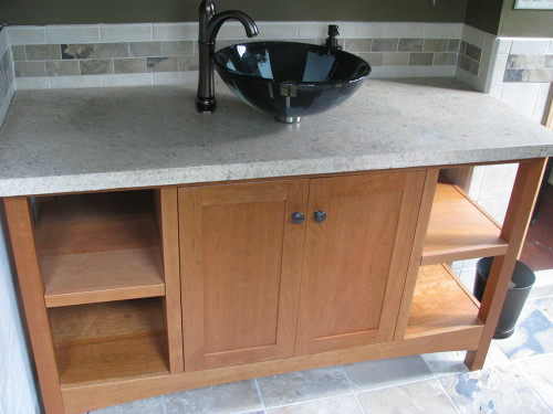 """This particular open style vanity is 57"""" wide, made from solid cherry, has two shaker flat panel doors in the center and two 14"""" solid shelves on each side. It also has square legs and arched base rails."""