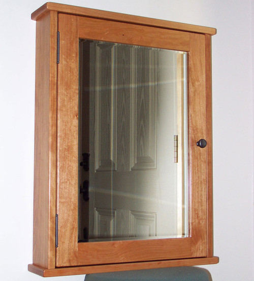 Surface mounted shaker style medicine cabinet with a mirrored door. Shown in cherry with oil  rubbed bronze hardware.
