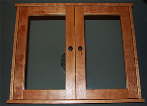 Surface mounted, shaker style, double door medicine cabinet with mirrored doors. Shown in cherry with oil  rubbed bronze hardware.