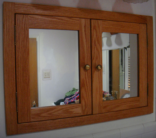 Recessed, shaker style, double door medicine cabinet with mirrored doors. Shown in red oak. The style is the same for unfinished.