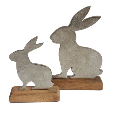 Two metal rabbits on wooden plinths