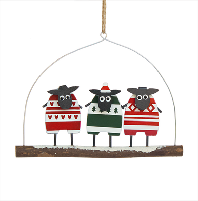 Three sheep all dressed in pattered jumpers standing on a branch
