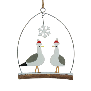 Two seagulls wearing hats standing on a branch underneath a snowflake.