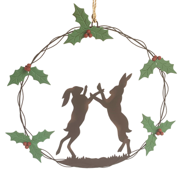 Two Boxing Hares in a circular wreath surrounded by holly and berries.