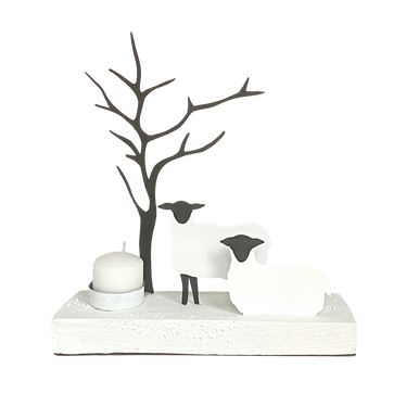 Two sheep stand and sitting next to a tree with bare branches and a candle holder at the end.