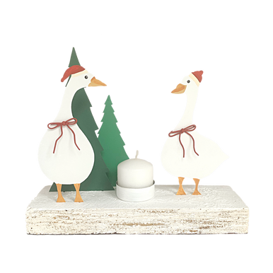Two geese standing in hats with a candle holder between them