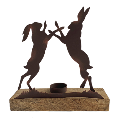 Two boxing hares standing on a wooden block with a candle holder in the middle.