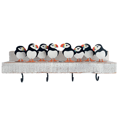 A pack of puffins standing on a white plinth with four hooks underneath.