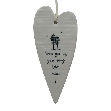 """Beautiful white ceramic hanging heart decoration with the words """"Never give up, great things take time"""" illustratively written alongside trees and birds sketch."""