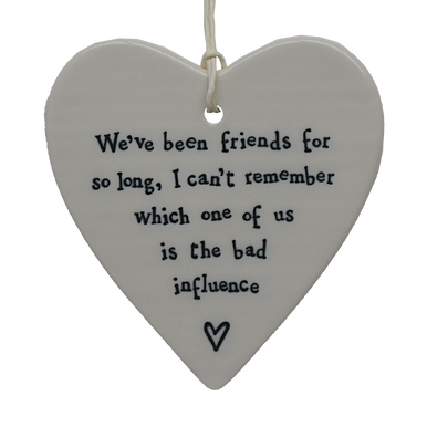 """Beautiful white ceramic heart decoration with lovely wording that says """"We've been friends for so long, I cant remember which one of us is the bad influence"""" along side a small heart illustration."""