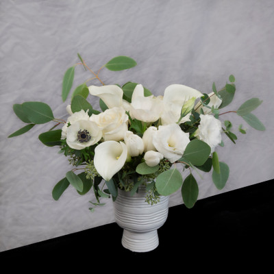 white flowers with textured greenery in a textured white ceramic vase