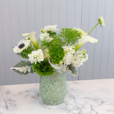 Local pottery vase with seasonal white and green flowers