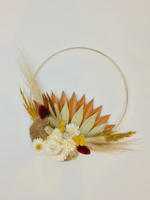 gold hoop with everlasting dried florals in tones of beige, camel, and burnt orange