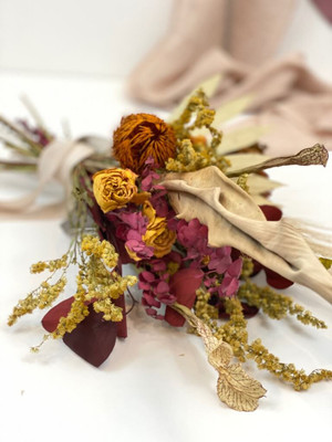 bundle of dried flowers in autumnal tones tied with raffia for a table setting or vase