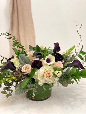 a decadent floral in cream, white, plum mixed with various foliage and wispy branches. This floral reaches out and is a lovely addition to a dining or coffee table for seattle flower delivery by juniper flowers