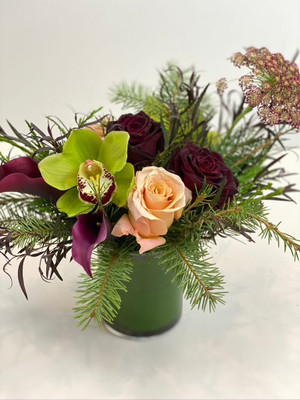 A small but sweet floral consisting of high end blooms mini callas, roses and orchids mixed with the evergreen foliage of fir, pine, and a wisp of agonis for a natural touch for seattle flower deliver by juniper flowers