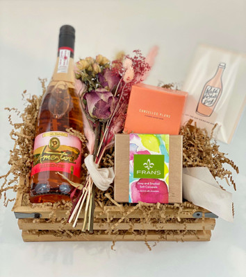 """A gift crate for the Rosé lover! Includes Ameztoi Rosé, Cancelled Plans candle called Do Not Disturb, a dried bundle of rose pink dried flowers, 7piece Gray Salt Caramels from Fran's Chocolates, and a sweet letterpress card from Dahlia Press that says """"Let the Day Drinking Begin"""" Seattle flower delivery by Juniper Flowers"""