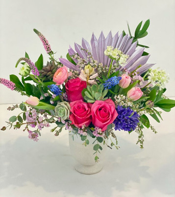 We choose the most beautiful blooms of the Spring Season. Local bulb flowers such as hyacinth, ranunculus, and tulips are combined with fun succulents and fan palms for textural interest.Seattle flower delivery by Juniper Flowers