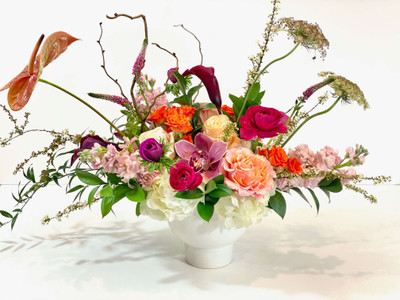 Funky Mom Seasonal, fun and quirky flowers come together in this white compote style vase. Some of the main players are roses, stock, orchids, and tendrilly buds such as spirea and chocolate lace. We'll choose the best blooms to make this a wonderful gift! Seattle flower delivery by Juniper Flowers