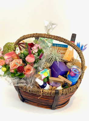 Deluxe Mother's Day gift basket  First off, it's big! This deluxe basket contains a $125.00 designers choice floral, refreshing Hydrosol face/body mist, botanical oil essence, seed starter kit, handmade soap, air plants, Cancelled Plans candle, Dahlia Press notepad, a variety of Fran's chocolates and your choice of champagne or wine! Very indulgent gift with our favorite hand selected items. Seattle flower delivery by Juniper Flowers
