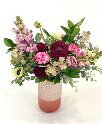 Al Fresco A mid height floral with stately blooms in pinks and white to complement the rose toned vase. Snapdragons, scabiosa and ranunculus mix it up with fresh eucalyptus and ruskus foliage. Perfect for dinner on the patio!Seattle flower delivery by Juniper Flowers