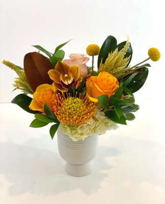 Golden Hour  We are headed into fall! This autumn inspired beauty contains magnolia foliage with it's rich green leaf and suede-like brown underside. Complementing flowers are roses, pincushion protea, orchids and craspedia. Bring on sweather weather! Seattle Flower delivery by Juniper Flowers