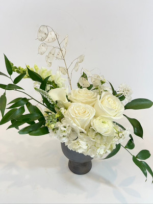 October + Opals White hydrangea, callas, snapdragons, and roses are wonderful expressions of elegance, elevated in a modern metallic toned vase. Accented with dried lunaria for it's opalescence, this floral appeals to lovers of the October gemstone! Seattle flower delivery by Juniper Flowers