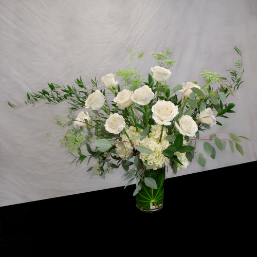 We've chosen a creamy white rose that fully opens and has fresh fragrance. Accenting and feathery greens such as italian ruskus and eucalyptus enhance the beauty of the long flower stems. This is a more traditional style. Choose from rose colors of white, red, peach, or berry. Seattle flower delivery by Juniper Flowers
