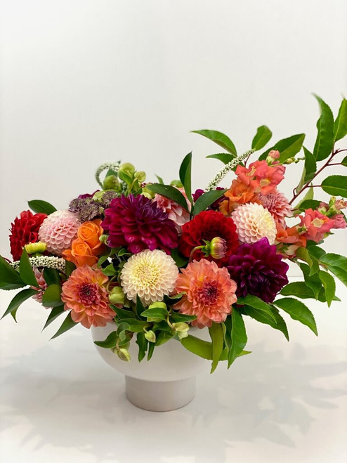 Dahlia Days  Summer is here and so are the dahlias. Our talented designers choose the best LOCAL dahlias and pair with greenery and accent flowers in a white ceramic compote vase. Seattle flower delivery by Juniper Flowers